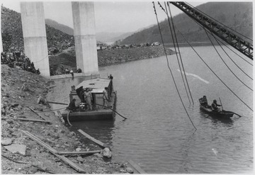 Workers make their way out into the water to repair the damage.Five workmen killed and four injured when the 300-ton span buckled and folded downward into the river. A week after the collapse the men began dismantling the twisted span, using a never before used technique by burning the steel beams with chemicals.