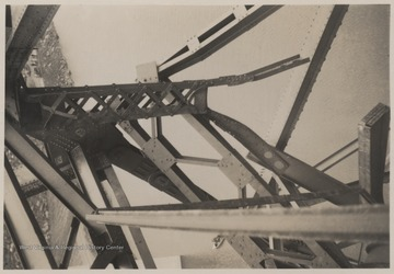 A close-up look at the bent bridge steel.A week after the collapse the men began dismantling the twisted span, using a never before used technique by burning the steel beams with chemicals.Five workmen killed and four injured when the 300-ton span buckled and folded downward into the mouth of Bluestone River.