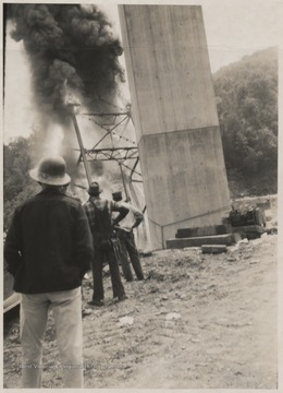 Three men observe the damage after the span of the bridge collapsed into the mouth of the Bluestone River.Five workmen killed and four injured when the 300-ton span buckled and folded downward into the mouth of Bluestone River.A week after the collapse the men began dismantling the twisted span, using a never before used technique by burning the steel beams with chemicals.