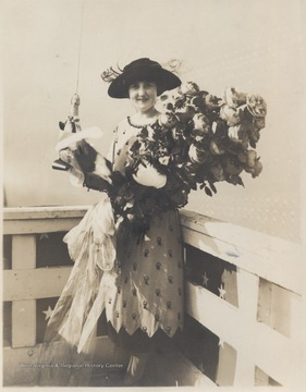 Alice Wright-Mann, of Mercer County, is pictured with a large bouquet of flowers and what appears to be a bottle of champagne.Ms. Wright-Mann sponsored the battleship which was built by the Newport News Shipbuilding and Drydock Co. of Newport News, Va. Wright-Mann was the daughter of a millionaire coalmine operator, Isaac T. Mann.