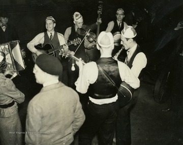 "The group of musicians is likely the Rhythm Rangers. These musicians, like all employees of the ""It's Wheeling Steel"" radio broadcast, were either employees or family members of employees of the Wheeling Steel Corporation. This radio broadcast was company advertising executive John L. Grimes idea to promote both the company's product and its employees. It began broadcasting in 1936 and ended in 1944."