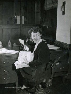 "Caption on back of photograph reads: ""Part of Regina Colbert's lunch hour is devoted to catching up on correspondence with service men at home and overseas. The ""Singing Secretary"" writes weekly to a number of men in uniform."" Regina Colbert was a performer on the ""It's Wheeling Steel"" Radio broadcast. This broadcast was ran exclusively by Wheeling Steel Corp. employees and family members, but as the program grew in popularity they began to hire performers with professional backgrounds, like Regina Colbert. However, in order to comply with his rule of an all employee only run program, he would hire these professionals to work in the offices for a period of time. In Colbert's case, she was hired to work as a secretary in the advertising department."