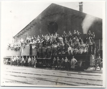 Engine No. 7 sitting beside stall No. 1 of the roundhouse. A group of unidentified workers stand on along the tracks and sit on the train.