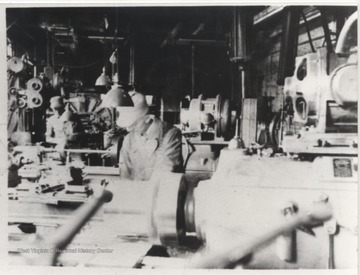 Harold E. Price pictured at lathe in foreground near K. V. Angell, who is pictured in the background to Price's right.