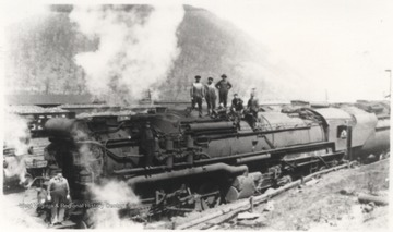 Six unidentified men are pictured on top of the steaming train.