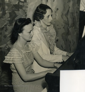 "Caption on back of photograph reads: ""Molly Staten and Eleanor Bowman Lynn rehearsed several weeks on their piano duet. They are stenographers from the main office of Wheeling Steel Company."" Like all performers and employees on the ""It's Wheeling Steel"" broadcast, all were also employees or family members of the Wheeling Steel Corporation. They were radio's first all employee only broadcast."