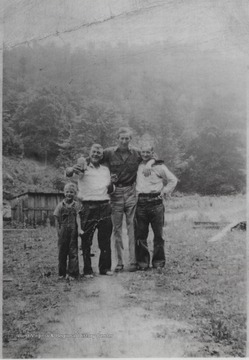 Pictured from left to right is Donald Meador, his father Cecil Meador holding up a bottle, Oris Cook, and Pee Wee Woolridge.