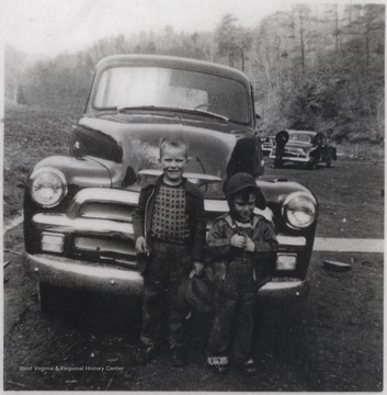 Cecil Meador's sons, Nanes and unknown, pose in front of a parked car.