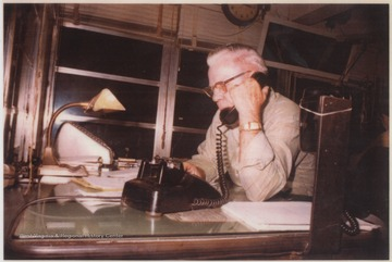 Russell, father to Joe Neely, is pictured sitting at a desk while on a phone call.
