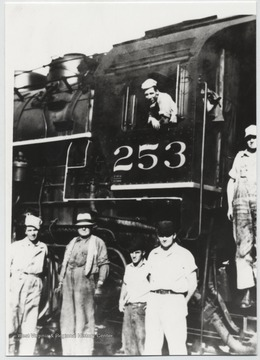 "Pictured from left to right is J. E. Burdette (brakeman), O. C. ""Battle Ax"" Allen (conductor), Hobart Akers (brakeman), and Jack Sweeney (brakeman) with N. B. Allen (engineer) on the steps and C. L. Keaton (fireman) in the cab."