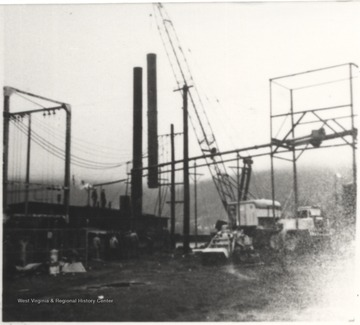 A crane lifts new smoke stacks to replace the old ones provided by Erie Iron Works in Erie, Pa. in 1924.