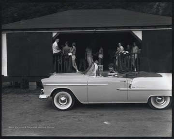 An unidentified woman sits in a car next to a pavilion filled with people in summer clothes and bathing suits.