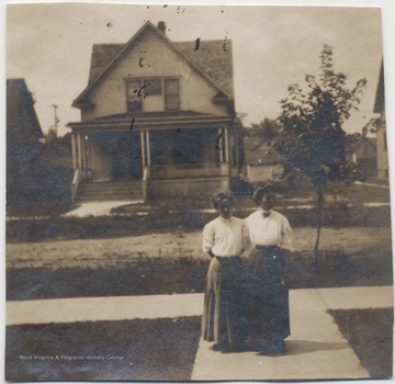 Family members of James H. Miller are pictured on the sidewalk in front of a home.