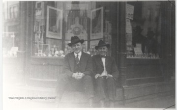Two unidentified men sit on a step of the building which is located on the corner of Third Avenue and Temple Street.
