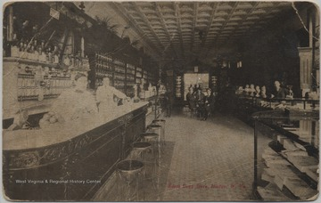 Postcard published by Tom Jones of Cincinnatti, Ohio. Three unidentified men stand behind the counter on the left while a group of men sit at a table in the background.