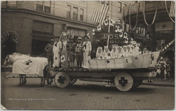 Horses draped in Red Cross flags pull a cart covered in uniformed persons and decorated seats. The drug store is pictured in the background.