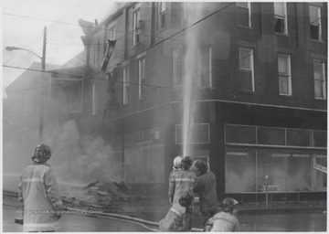 A group of unidentified firemen fight the fire inside a three story brick building originally housing Rose's Drug Store, Co.