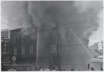 Smoke billows from the windows of the three-story, brick building originally built to house Rose's Drug Store, Co.