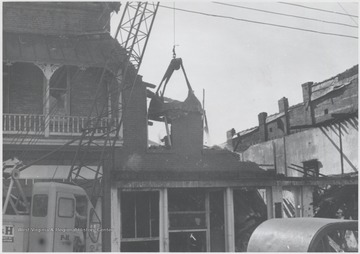 View of the broken building following a fire. The three-story, brick building was originally erected to house Rose's Drug Store, Co.