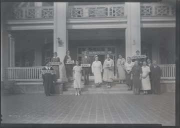 A group of unidentified school teachers and nurse stand in front of the building holding signs that read a variety of school subjects.