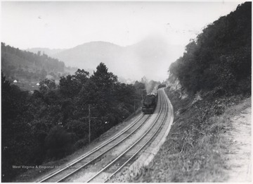 A train winds along the track placed next to New River.