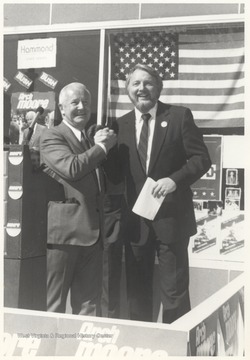 Governor Moore, left, shakes hands with an unidentified associate. Moore serves as governor from 1969-1977.