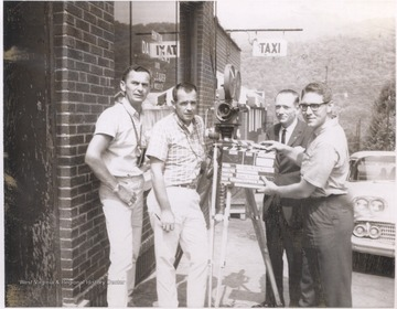 Four unidentified men stand with film equipment during them making of the movie about Hinton's story.