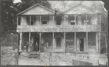Five men and a woman stand on the porch of the inn.