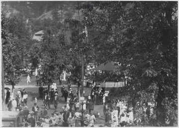 A crowd gathers across the lawn and around a pavilion decorated with American flags.