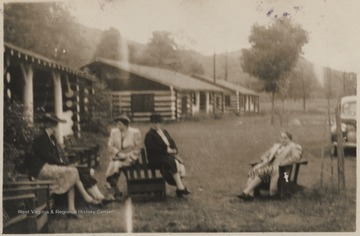 A group of women sit outside the building where the meeting is located. Subjects unidentified.