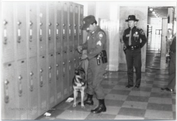 Law enforcement officials stand by while a dog is led down the hallway in search of drugs.