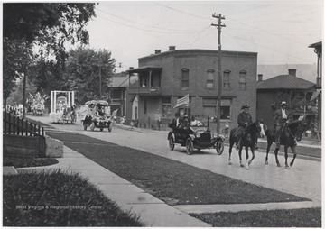 Two men on horses lead automobiles and parade floats down Temple Street.
