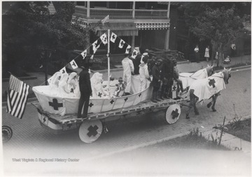 Uniformed soldiers and nurses sit in what appears to be a Red Cross parade float drawn by horses down Temple Street.