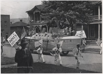 A float shaped as an artillery tank makes its way down Temple Street while young boys dressed as sailors carry American flags and signs for the drugstore.