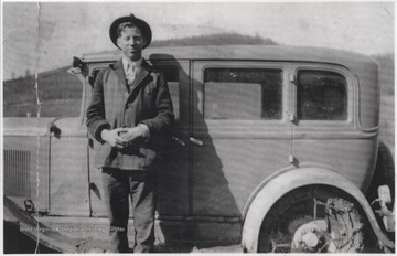 Adkins pictured beside an automobile.
