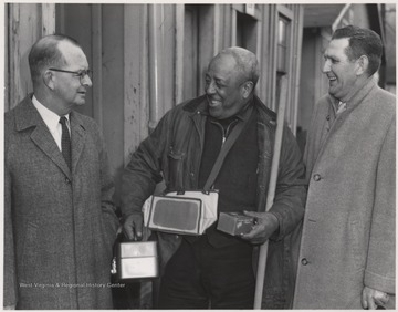 The C. & O. engineer Burdette, pictured on the far right, laughs beside two unidentified men.