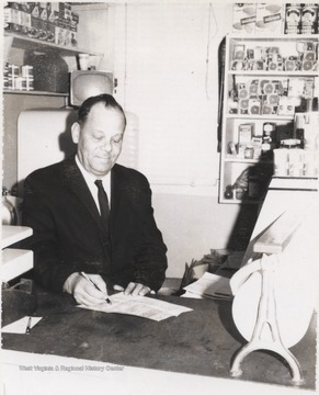 Burdette pictured signing a document.