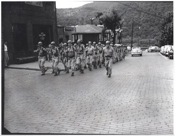 A group of unidentified soldiers carry their rifles up the brick road.