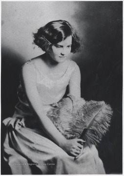 Johnson pictured in fashionable attire holding a feather.
