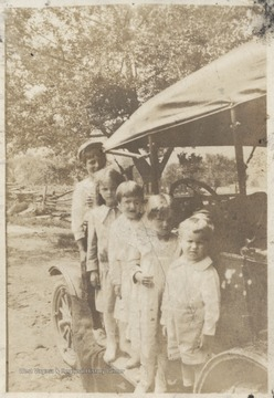 Phillip Shumate's children, of which one is Mary E. Shumate, are pictured balancing on the side of an old-fashioned automobile.