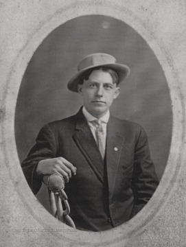 Oran, brother to H. D. Thompson, is pictured sitting on a chair in a suit and hat at an unkown location.