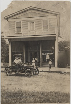 Three men sit outside the store in an old-fashioned automobile while others stand outside the shop. Subjects unidentified.