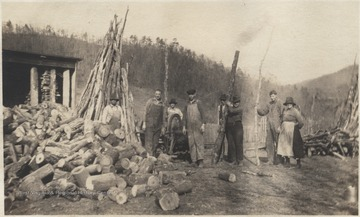Emma Walker Meador on the far right with Matt Cook to her right. The rest of the unidentified men haul sticks and wood across the land. The farm is now known as Meador Camp Ground at the Bluestone State Park.