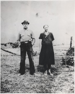 Mr. and Mrs. Ward stand in front of a fence.