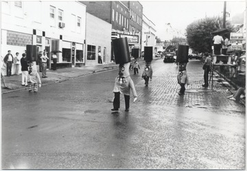 Men with painted stomachs and costumes walk down Ballengee Street. Subjects unidentified.