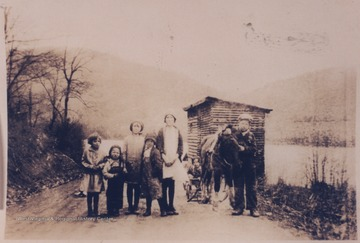 Pictured, from left to right, is Madeline Wood, Clarence Wood, Ruby Wood, Billy Wood Noble, Mary Wood, Elmer Noble, Homer Noble, and Fred Noble in the wagon.