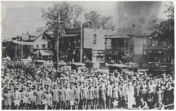 A large group of uniformed soldiers pose together behind decorations. In the background is Second Avenue and Temple Street. Subjects unidentified.