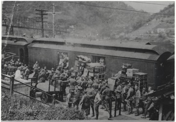 A crowd of men in uniform gather around the passenger train and load their luggage.