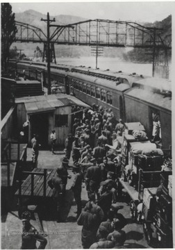 A group of men crowd the passenger train at Hinton Station while loading their luggage.