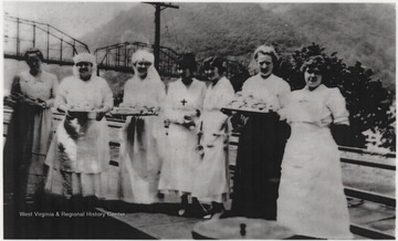 Seven unidentified women hold trays of food as they await the troops to pass through Hinton Station.